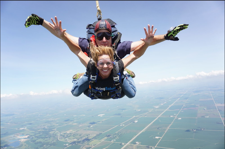 Heather Thomas skydiving while wearing a HiringSolved tshirt