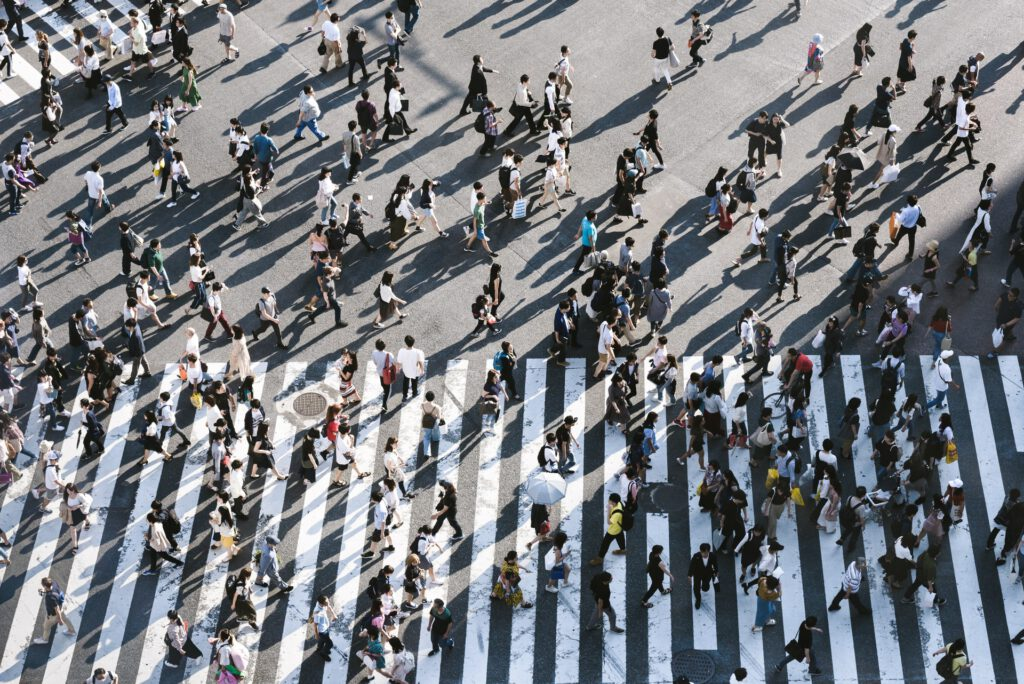 Image of crowd of people crossing a street with a crosswalk painted on the ground