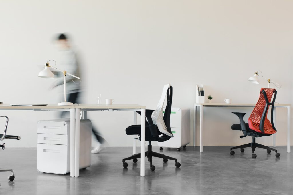 Image of blurred person moving in an office space with chairs in the forefront