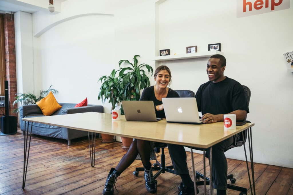 Two people sitting at a desk smiling at two computers