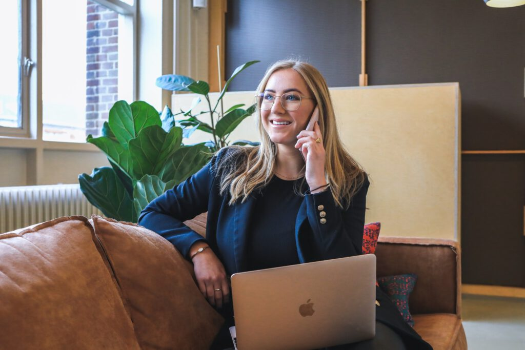 White woman talking on the phone with computer on their lap